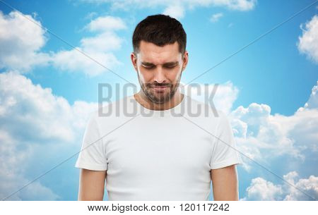 emotion, sadness and people concept - unhappy young man over blue sky and clouds background