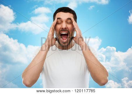 emotions, stress, madness and people concept - crazy shouting man in t-shirt over blue sky and clouds background