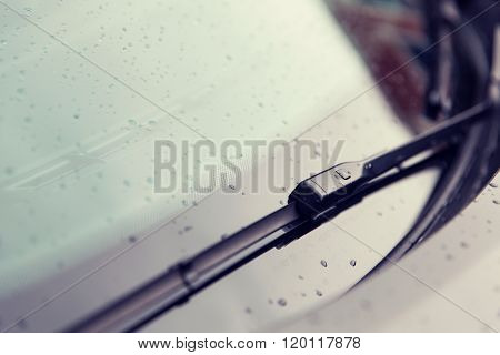 rainy weather and vehicles concept - close up of windshield wiper and wet car glass