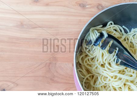 Italian spagetti cooked in a pan isolated on wooden table