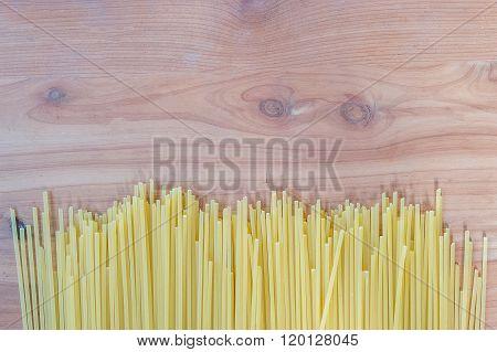 Uncooked pasta spaghetti macaroni isolated on wood table