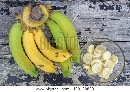 A banch of bananas and a sliced banana in a glass cup on wooden vintage table