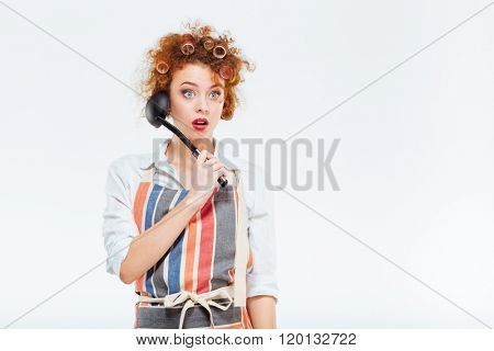 Amazed redhead housewife with curly hair in apron holding soup ladle isolated on a white background