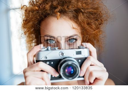 Attractive redhead curly young woman photographer using old camera