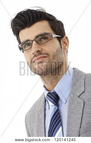 Closeup portrait of handsome young bristly businessman in glasses, looking up. Photographed from below.