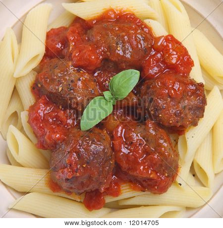 Meatballs in tomato sauce with rigatoni pasta.