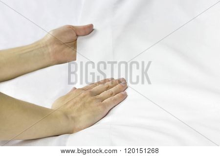 A pair of hands smoothing out a bed sheet.
