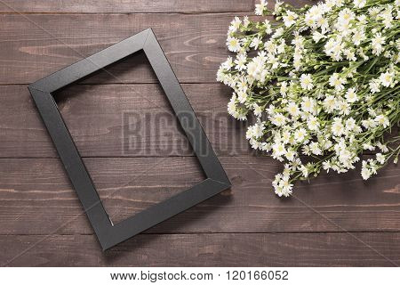 Picture Frame And Cutter Flowers Are On The Wooden Background