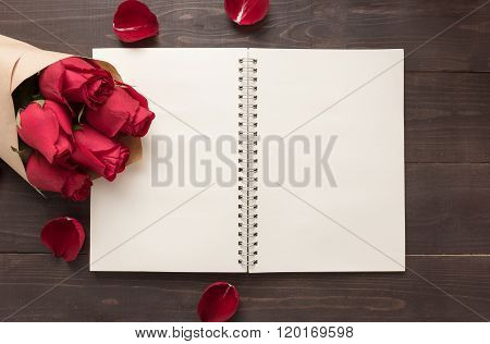 Red Roses Flower With The Notebook Are On The Wooden Background