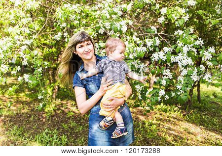 Happy young woman and little son in the blooming spring garden. Mothers day holiday concept