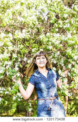 Beautiful spring woman in blooming tree