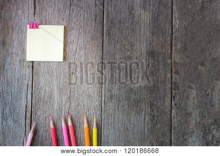Yellow Note Paper On Wooden Background With Colored Pencils.
