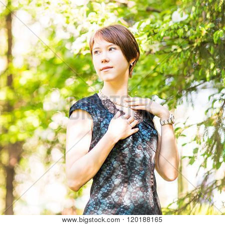 Romantic young woman in the spring garden among apple blossom