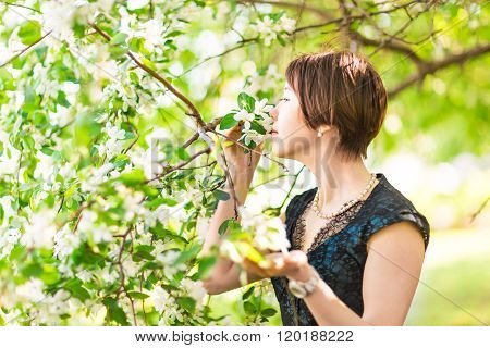 Portrait of young woman  in the flowered garden in the spring time. Almond flowers blossoms.