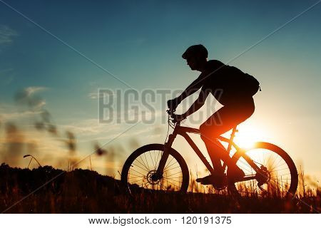 Man Cyclist with bike on sunset