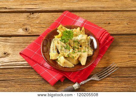 plate of marinated artichokes on red dishtowel