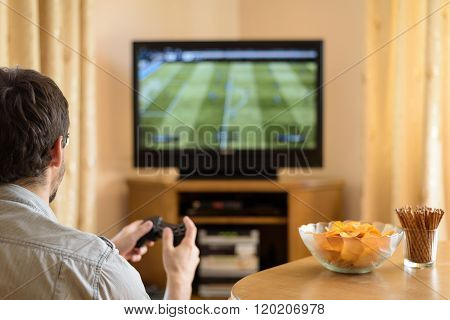 Man Playing Soccer Video Game On Console In Home - Stock Photo