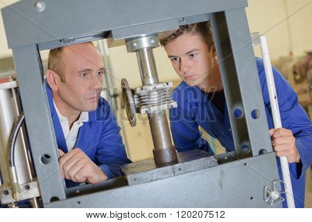 Two men looking at cylinder in vertical vice