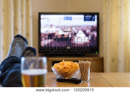 Man Watching Tv (television) War Movie With Feet On Table