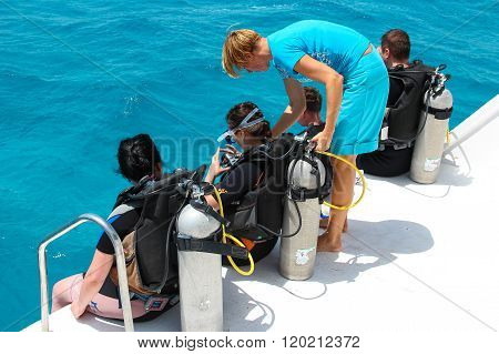 The woman diving coach gives instructions to beginners before diving from the boat, red sea