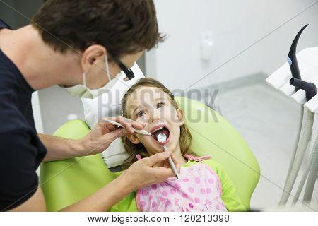 Girl Sitting On Dental Chair On Her Regular Dental Checkup