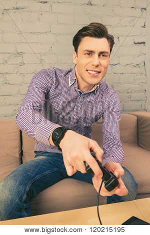 Excited Handsome Man Sitting On Couch And Playing Video Games
