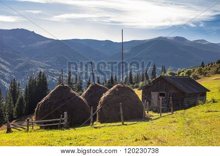 Cute Wooden House And Reaps On Mountains Background..