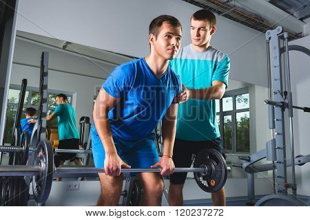 Muscular Man Lifting Deadlift In The Gym with instructor