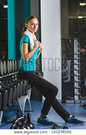 Woman girl resting at the gym On The Bench