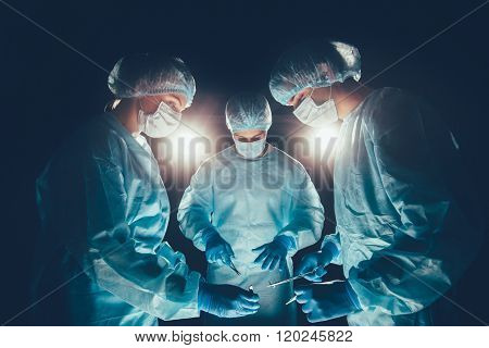 Medical team in hospital performing operation. Group of surgeon at work in operating theatre room. healthcare Bright light in the frame artistic effect poster