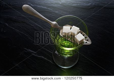 absinthe in pontarlier glass and spoon with sugar cubes poster