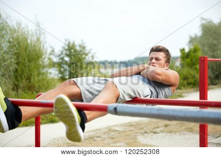 fitness, sport, exercising, training and lifestyle concept - young man doing sit up on parallel bars in summer park poster