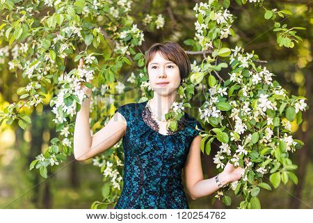 Spring girl portrait. Asian woman smiling happy on sunny summer or spring day outside in flowering t
