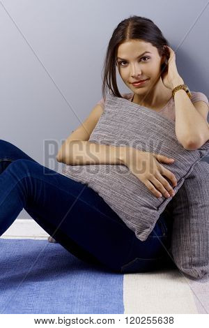 Young woman sitting on floor at home, hugging pillow, smiling, looking at camera, hand in hair.