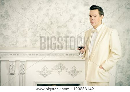 Handsome well-dressed mature man in elegant white suit stands by the fireplace.