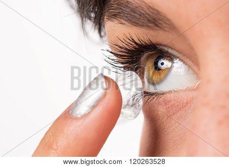 Young woman putting contact lens in her eye. Macro shot.