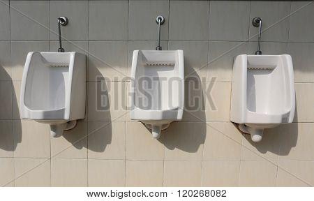 White Ceramic Of Urinals In Men's Bathroom.