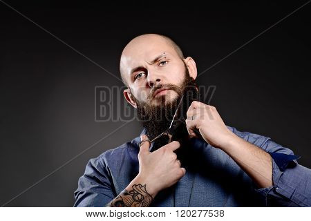 Portrait Of  Man Cutting His Beard With Scissors And Looking At Camera