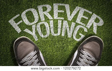 Top View of Sneakers on the grass with the text: Forever Young