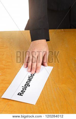 Hand Holding Resignation Letter On The Desk Of The Boss.