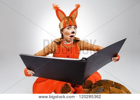Young woman in the image of red squirrel with big book