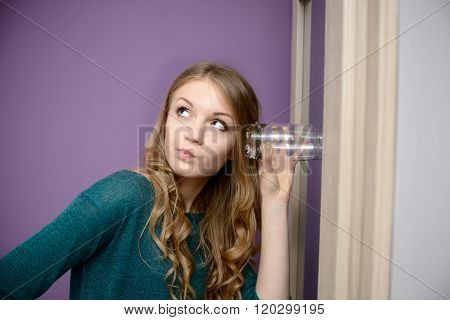 Young blonde woman listening in to a conversation with a glass pressed against her ear