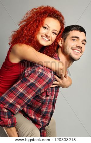 Happy young couple in love embracing on grey background