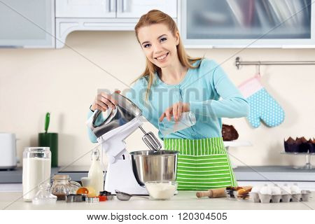 Young woman adding milk to a food processor to male a dough