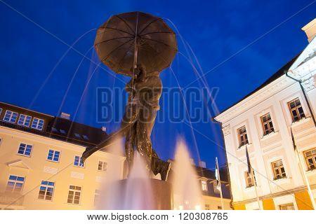 Statue of kissing students under umbrella