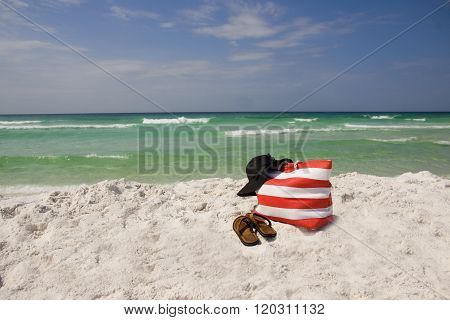 A beach bag hat and sandals lying on the beach.