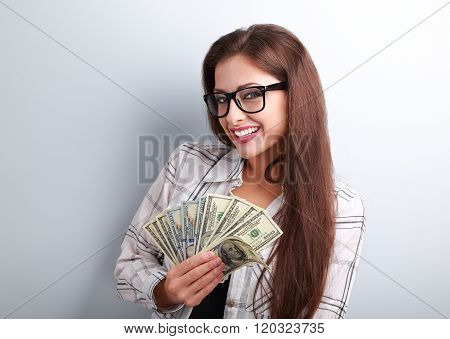 Happy Business Woman In Glasses Holding Dollars In Hand With Toothy Smiling On Blue Background