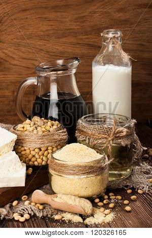Soy products (soy flour, tofu, soy milk, soy sauce) on a wooden background. rustic style