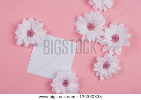 white flowers on a pink background with white notepad