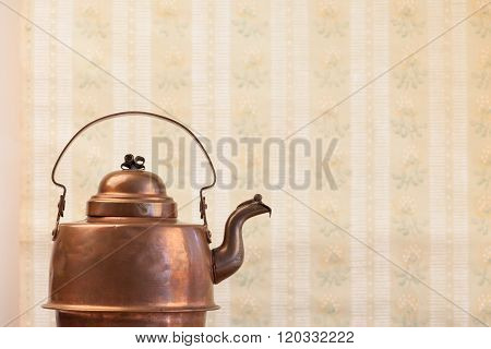 antique vintage copper kettle on the background of old wallpaper